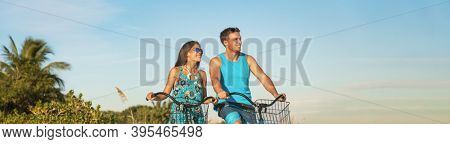 Biking tourists couple cycling enjoying summer outdoor sport activity banner panoramic. Young woman and man riding bicycles on Caribbean vacation. Active people lifestyle happy.