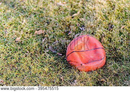 One Deflated Dirty Orange Basketball On Grass.
