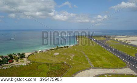 Runway At Denpasar International Airport In Bali, Indonesia. Runway Reaching Into The Ocean. Aerial