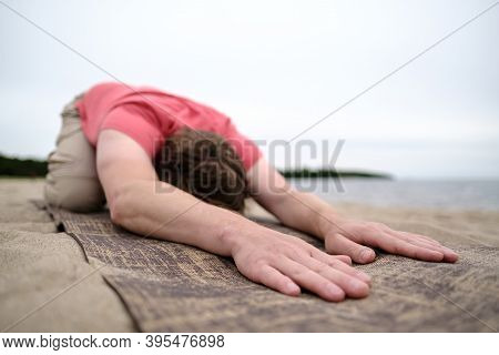 Man Does Yoga, He Does The Exercise In Child Pose, Balasana, Relaxes And Stretches Lying On A Rug, O