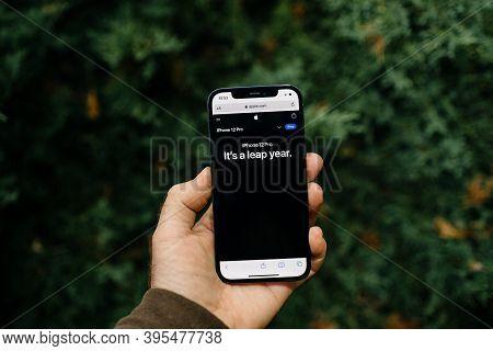 Paris, France - Nov 11, 2020: Website Showing Male Hand Holding Against Juniper Tree Background Appl