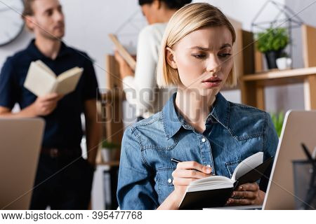 Blonde Woman Writing On Notebook While Looking At Laptop In Office With Blurred Multicultural Co-wor
