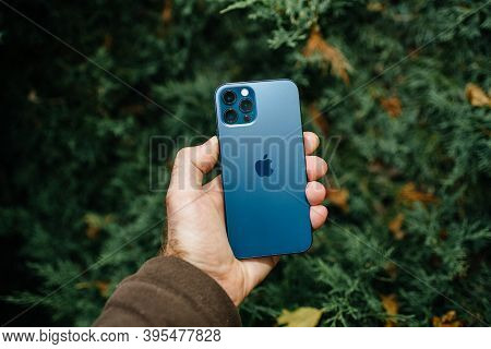 Paris, France - Nov 11, 2020: Male Hand Holding Against Juniper Tree Background New Apple Computers