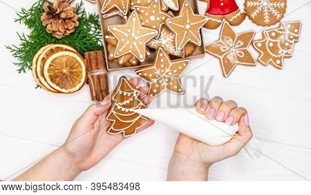 Female Hands Paint Christmas Gingerbread Cookies. Woman Hands Paint A Xmas Treats, Ornaments. Hands