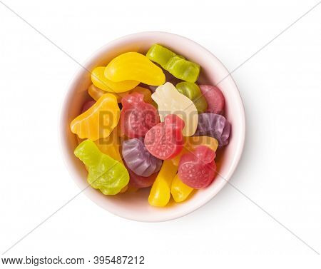 Colorful fruity jelly candies isolated in bowl on white background.
