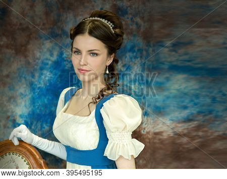 Beautiful Girl In A Historical Dress In The Empire Style Of The Early 19th Century On An Unusual Blu