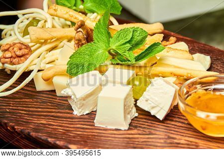 Cheese Platter With Feta, Parmesan, Mozzarella, Cheese Sticks, Braid Cheese With Honey And Nuts On T