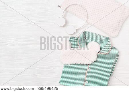 Sleepwear For Slumber. Women Pajama With Stripes Blue Color, Headphones, Sleeping Mask On White Wood