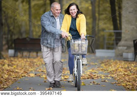 Happy Middle Aged Couple With Bike In Autumn Park. Elderly Cheerful Husband And Wife On A Walk.