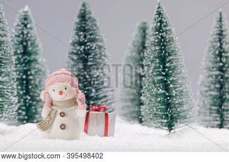 Small cute toy snowman with gift in forest in snow Christmas card design