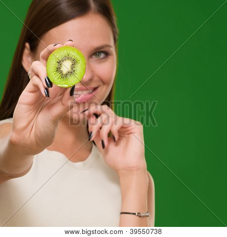 Portrait Of A Young Woman Holding Kiwi On Green Background