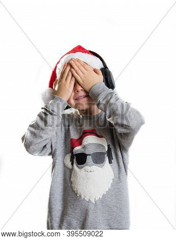 Little Boy In Santa Claus Hat Closed Eyes With Hands In Anticipation Of A Christmas Miracle And A Gi