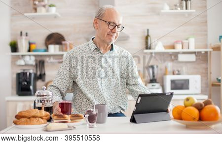 Senior Person Browsing On Tablet Pc In Kitchen During Breakfast Having A Healthy Lifestyle. Elderly