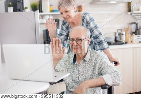Invalid Man And Wife Saying Hello To Their Family. Disabled Senior Man In Wheelchair And His Wife Ha