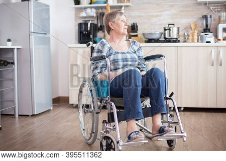 Depressed Handicapped Senior Woman In Wheelchair From Leg Injury. Elderly Disabled Pensioner In Reha