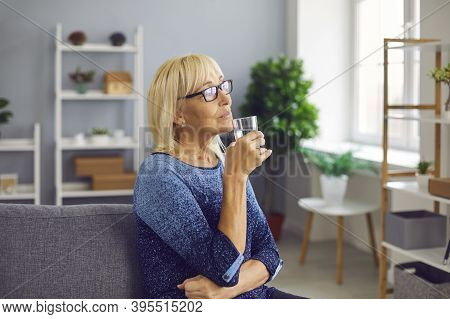 Pensive Senior Woman Drinking A Glass Of Pure Fresh Water To Stay Hydrated And Healthy