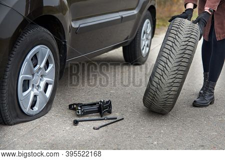A Young Woman Rolls Spare Tire Near Her Car With A Flat Tire, Trouble On The Road.
