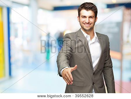 Portrait Of  Young Businessman In A Suit Holds Out His Hand For A Handshake, Indoor