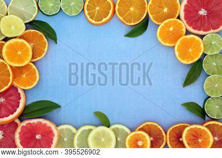 Healthy high fibre citrus fruit border for immune boost with oranges, lemons, limes & grapefruit, high in antioxidants, anthocyanins, lycopene & vitamin c. Natural health care concept on mottled blue.