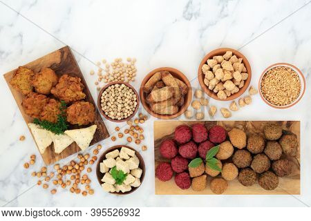 Healthy plant based food for a vegan diet with a variety of tofu balls & sausages, onion bhajis, samosas, soybeans, tvp & bean curd. Ethical eating concept. Flat lay on marble.