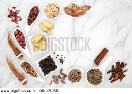 Traditional Chinese herbal medicine for good health with fresh & dried herbs & spice on marble background. Natural health care concept. Top view, flat lay.