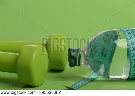 Healthy Lifestyle And Low Calorie Drink Concept. Dumbbells In Green