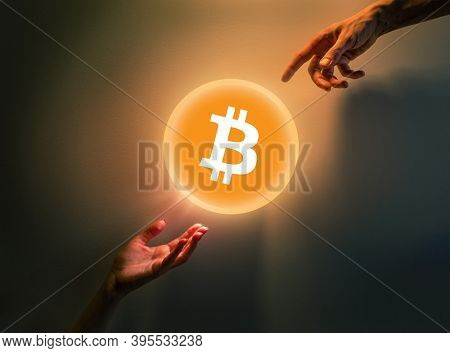 Creation of Bitcoin digital currency bubble. Hands pointing at shiny coin over dramatic dark background.
