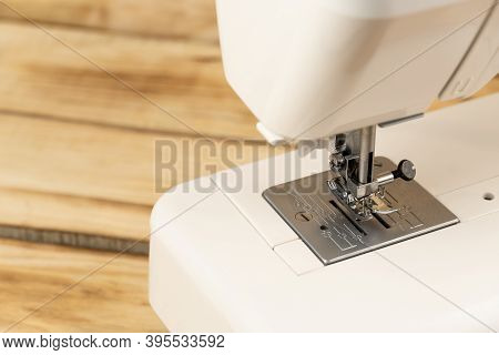 Close-up Of A White Sewing Machine On A Wooden Background. Sewing And Needlework, Sewing On A Sewing