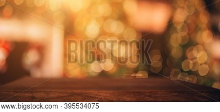 Beautiful Blurred Christmas Background. In The Foreground Is A Wooden Table. In The Background There