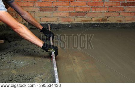 Worker screeding indoor cement floor with screed