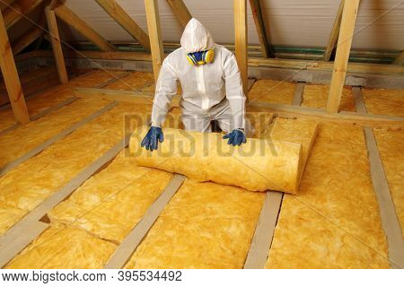 Worker in protective respirator insulating glass wool insulation in wooden construct.