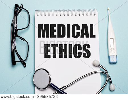 Medical Ethics Written On A White Notepad Next To A Stethoscope, Goggles, And An Electronic Thermome