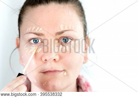 Young Woman Applies Concealer Makeup On Her Face With A Small Brush. Similar To Foundation, Or Color