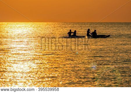 Couples Enjoy Golder Sunset While Kayaking Out On The Sea