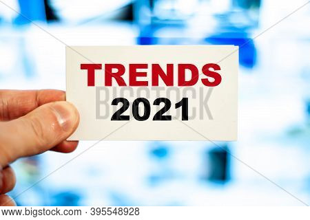 2021 Planning Business Concept. A Man's Hand Holds A Business Card With The Inscription Trends 2021.