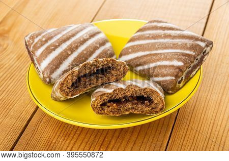 Two Whole Striped Gingerbreads And Broken Gingerbread With Jam In Yellow Saucer On Wooden Table