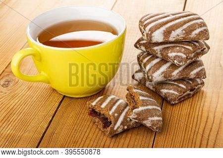 Yellow Glass Cup With Tea, Broken Gingerbread With Jam, Whole Striped Gingerbreads On Wooden Table