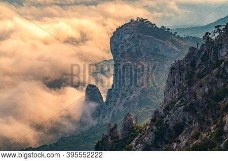 Majestic Orange Sunset Over The Rocky Mountains And The Valley In Fog And Clouds. Creamy Fog Covered