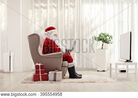 Santa claus working on a laptop and sitting in an armchair in a living room at home