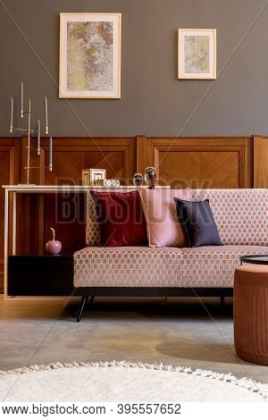 3. Stylish Interior Of Living Room With Design Pink Velvet Sofa, Elegant Pouf, Coffee Table, Posters