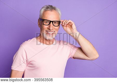 Photo Of Pensioner Grandpa Hold Specs Look Camera Smiling Wear Eyewear Pink T-shirt Isolated Purple