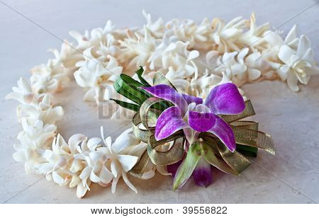This tropical still life is a Hawaii Lei made of white tuberose flowers a purple orchid and ribbon. It is lying on a light surface. poster