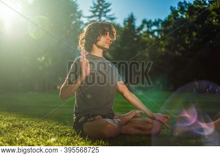 Young Handsome Man Practicing Yoga In The Evening Park. Sun Flares And Rays. The Lotus Position Of Y