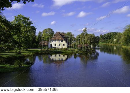 A Two-storey House On The Shores Of Lake Jaunpils On A Clear Sunny Day. Beautiful Lawn In Front Of T