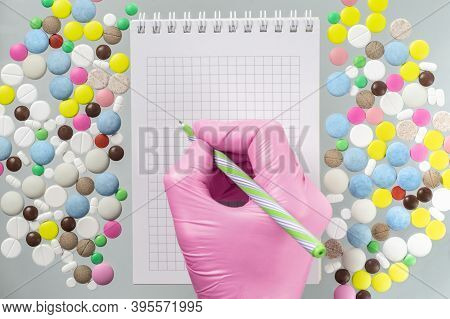 Doctor Or Pharmacist Writes In Notebook On The Background Of Multicolored Pills