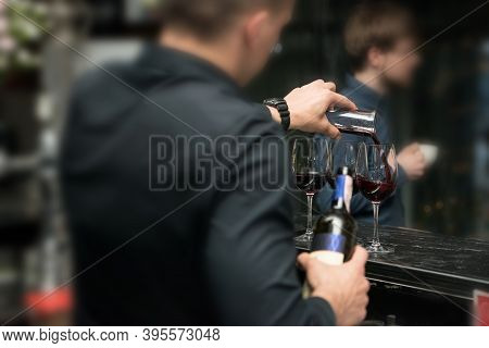 Barman Pouring Red Wine Into Glasses In Detail