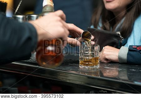 Barman Hand Pouring Strong Alcohol Into A Cocktail Glass Using A Professional Bartender Tool On