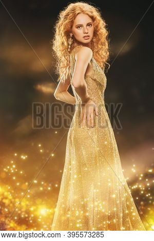 Festive evening dress. Portrait of a beautiful red-haired woman in a luxury golden dress surrounded by festive golden lights. Jewelry. Makeup and hairstyle.