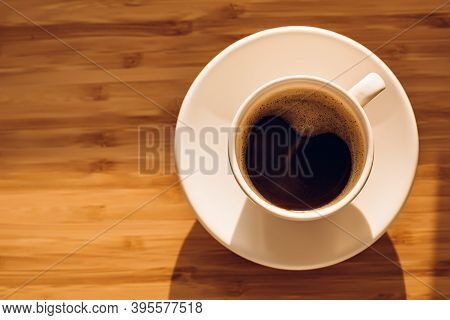 Cup Of Black Coffee On Bamboo Desk In Morning Sunlight.