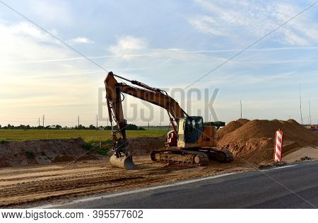 Excavator On Earthworks And Road Construction In City. Temporary Traffic Regulation From Carrying Ou